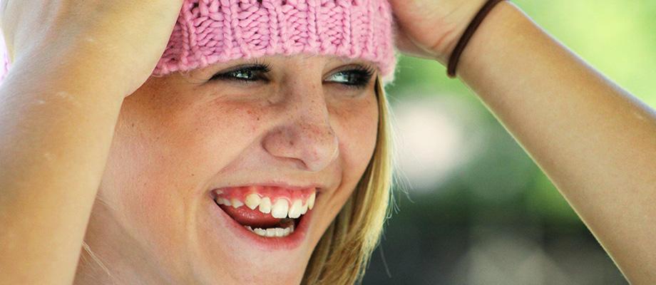 une petite fille rit avec un bonnet rose